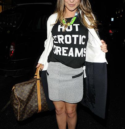 Звезда британского реалити-шоу «Золотая молодежь Челси» Луиз Томпсон    продемонстрировала фанатам черную майку «Горячие эротические сны» на вечеринке Shop To The Beat в Лондоне в марте 2013 года.