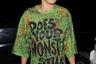 Британскую певицу Риту Ору сфотографировали в Лондоне в топе с зеленым принтом под кожу рептилии. На ней также были лосины в тон и кислотно-розовая шапка-балаклава. «Тебя все еще одевает твой монстр?»— написано на футболке Оры.