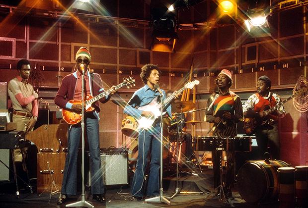 Боб Марли и The Wailers во время живого выступления на программе The Old Grey Whistle Test канала BBC в 1973 году. Питер Тош (второй слева) в своей неизменной шапочке и темных очках, Боб Марли (в центре) в клешеных джинсах и Банни Уайлер (второй справа) в панаме и футболке в раста-цветах.