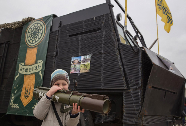 Ребенок с гранатометом на фоне эмблемы лагеря «Азовец»