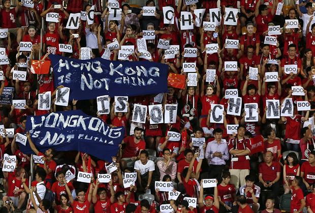 """Поняв, что действовать исподтишка в Гонконге не получится, а его жители готовы бороться за свои права, Пекин решил действовать осторожнее. В 2012-м в гонконгских школах появились уроки патриотического воспитания, на которых детям рассказывали, как нужно любить и ценить материковый Китай, а также о том, как результативно прошла Культурная революция и демонстрации на площади <a href=""""https://lenta.ru/photo/2018/06/04/tiananmen1989/"""" target=""""_blank"""">Тяньаньмэнь</a> в 1989 году, где, по разным подсчетам, правительство убило от 300 до 1000 человек. Жители города вновь не оценили попытки Пекина приблизить к себе Гонконг и <a href=""""https://www.bbc.com/news/world-asia-china-19529867"""" target=""""_blank"""">вышли</a> на протестные демонстрации. Коммунистической партии вновь пришлось пойти навстречу гонконгцам, привыкшим к тому, что с их мнением считаются."""