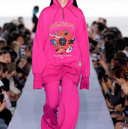 Ярко-розовый оверсайзный костюмчик показался бы детским, если бы не «расстрельный» принт на груди: мультяшные персонажи на фоне мишени.