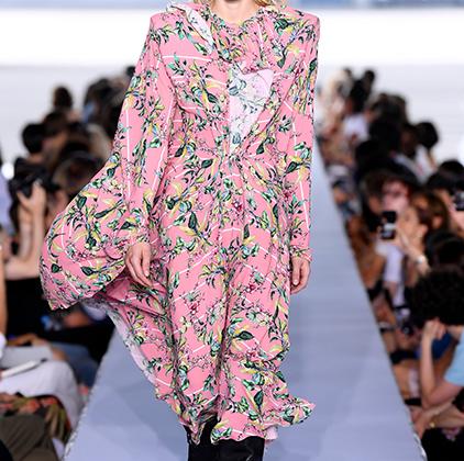 Розовое платье с пестрым принтом чем-то напоминает халаты, в которых грузинские матроны по-свойски, без церемоний развешивают белье в тбилисских двориках. По контрасту с этой уютной вещью — грубые, обитые металлом сапоги-казаки и полумаска, как из БДСМ-клуба.