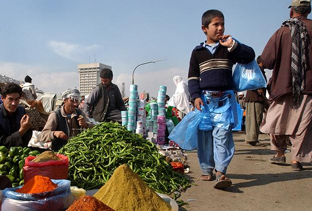 Афганский мальчик продает пакеты на улицах Кабула