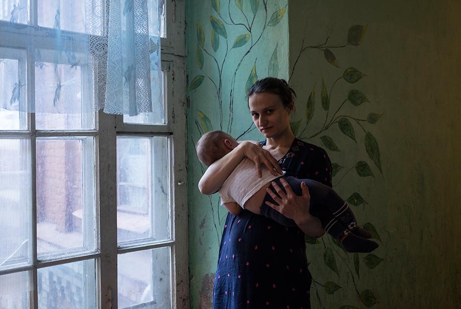 Гуля, 30 лет, позирует с младшим сыном на фоне рисунка в коридоре своего дома
