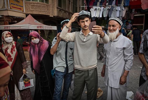 Уйгурский мужчина примеряет традиционную тюбетейку на базаре в центре Кашгара. Уйгуры составляют 81 процент населения города, а на титульный китайский этнос хань приходится лишь 18 процентов. Оставшийся один процент — дунгане, таджики, узбеки и сарыкольцы.