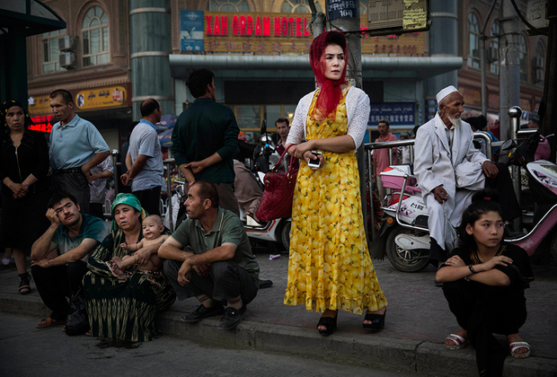 Кашгарцы в ожидании автобуса. Китайские власти регулярно проводят пропагандистские кампании среди местной молодежи, призывающие отказаться от ношения бороды и национального костюма. Тем не менее большинство кашгарцев остаются верны традициям.