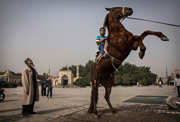 Уйгурский мальчик гарцует на лошади напротив главной достопримечательности Кашгара — мечети Ид Ках, крупнейшей в Китае. Она была построена в 1442 году, многократно перестраивалась и сейчас вмещает до 20000молящихся.