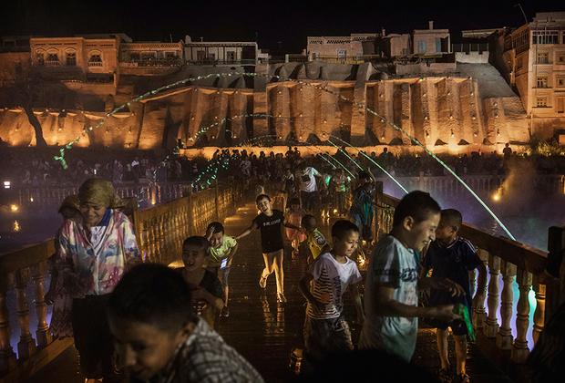 Юные кашгарцы радуются новому лазерному и водному шоу, устроенному прямо у стен Старого города. Это развлечение — часть государственной программы по развитию Кашгара в качестве туристического центра СУАР.