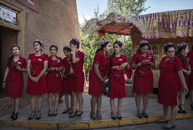 Гиды в национальных головных уборах выстроились в ожидании прибытия туристических групп. Несмотря на то что большинство уйгуров почти не говорит на китайском, гидов набирают среди местного населения.
