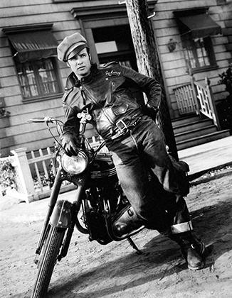 Законодатель байкерской моды — Марлон Брандо. Именно его герой в фильме «Дикарь» стал ролевой моделью для первого поколения байкеров и задал модные тренды для всей бунтарской молодежи 1950-х.