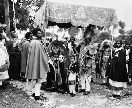 Под стать наряду была и церемония, в которой участвовали сотни людей. Чтобы новому императору было проще переносить жару, над его головой придворные держали роскошный балдахин.