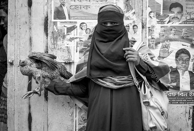 Фотография была сделана ранним утром в одном из людных районов Дакки, столицы Бангладеш. Художник был очарован прекрасно одетой женщиной, борющейся с только что купленной на рынке живой курицей. Он запечатлел ее закутанную фигуру на фоне стены, с которой на зрителей смотрят мужчины, столь контрастирующие с героиней снимка.