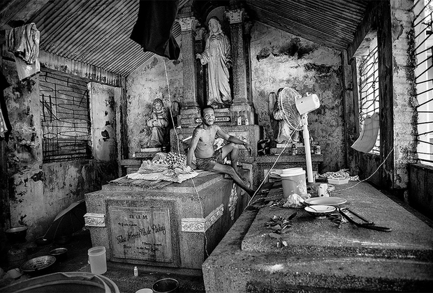 62-летний Рубен, герой фото, сидит на своей кровати. На протяжении последних 30 лет его дом — один из склепов на Северном кладбище города Манилы. Сейчас этот некрополь является последним приютом для миллиона усопших и одновременно выполняет функции жилища для десяти тысяч филиппинских семей. Из-за перенаселения бедняки вынуждены обустраивать быт прямо на могилах.