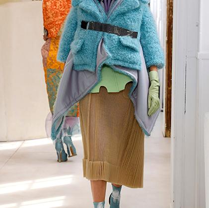 В Maison Margiela Джон Гальяно в полной мере демонстрирует свою страсть к экстравагантности, эпатажу и модной иронии. Привести на подиум недели haute couture модель не в вечернем платье, а в нескольких флисках и пуховиках, надетых один на другой, да еще и с синим лицом и в фирменной «копытной» обуви — вполне в его стиле.