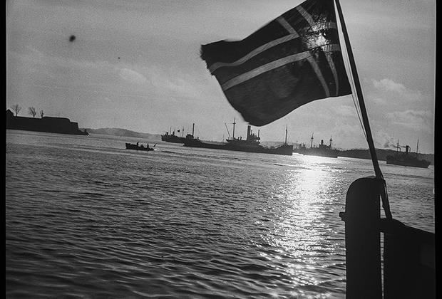 Норвежский флаг на борту судна, на фоне немецких кораблей и патрульного катера. Норвегия, 1940 год.