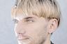 Нил Хариссон считает себя киборгом. Он страдает от ахроматопсии, редкой формы дальтонизма. В его череп вживлен протез под названием Eyeborg, который улавливает цвета и преобразует их в звуковые волны. Хариссон гордится тем, что стал первым человеком, который сфотографировался на паспорт с протезом. «H +» фокусируется на трансгуманизме, пропагандирующем использование науки и техники для повышения физических и умственных способностей людей.