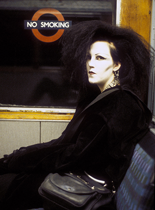 Типичная готесса первой волны в лондонском метро. Длинные растрепанные волосы, белила на лице, черная подводка глаз, красная помада, обилие серебряных украшений и, конечно же, total black.