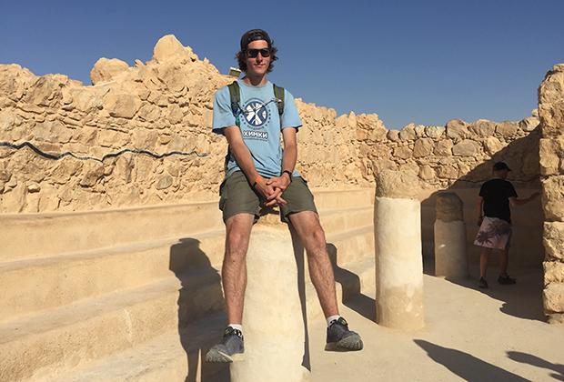 Жизнерадостный турист в руинах античной синагоги на Масаде
