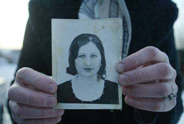 Подруга Эльзы Кунгаевой держит фотографию девушки, убитой Будановым. Село Танги-Чу
