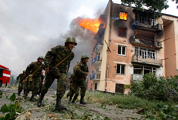 Грузинские солдаты в Гори на фоне здания, пострадавшего от бомбардировки. 9 августа 2008 года