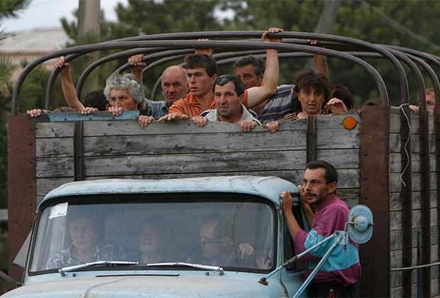 Грузинские беженцы покидают свои селения, расположенные недалеко от города Цхинвали. 8 августа 2008 года
