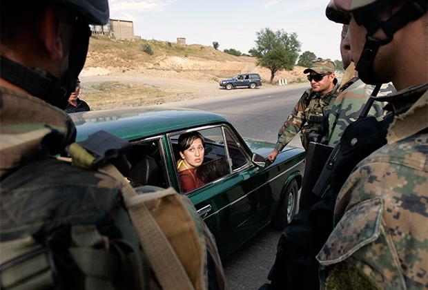 Грузинские военные проверяют машину беженцев, покидающих Гори. 13 августа 2008 года