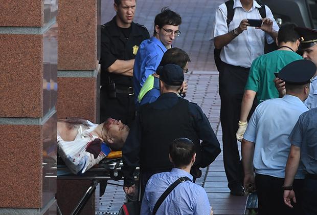 Сотрудники медицинской службы транспортируют раненого к автомобилю скорой медицинской помощи у здания Московского областного суда. Три члена банды GTA при попытке побега были убиты.