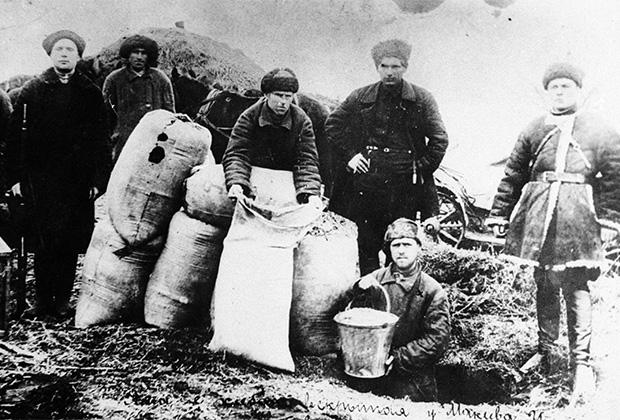 Члены рабочей бригады изымают скрытый кулаками хлеб