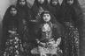 Дочь шаха Насера ад-Дина, круглолицая красавица Ахтар ад-Даула, позирует со служанками. Во второй половине XIX века персидские представления о красоте— как женской, так и мужской— заметно отличались от европейских. Знатные девушки не стремились похудеть и щеголяли пышными бровями, а порой и легкой растительностью на лице.