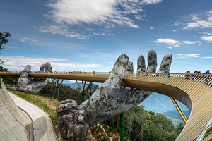 The Golden Bridge is lifted by two giant hands in the tourist resort on Ba Na Hill in Danang, Vietnam. Ba Na Hill mountain resort is a favorite destination for tourists