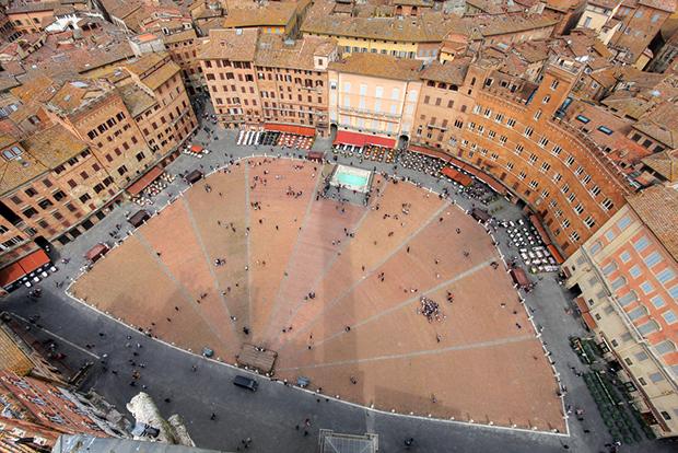 Вид на Пьяцца дель Кампо с высоты птичьего полета. По своей форме площадь напоминает ракушку. Гоночный круг состоит из четырех прямых и четырех поворотов —два крутых и два плавных. Падения, как правило, происходят на первом и последнем поворотах.