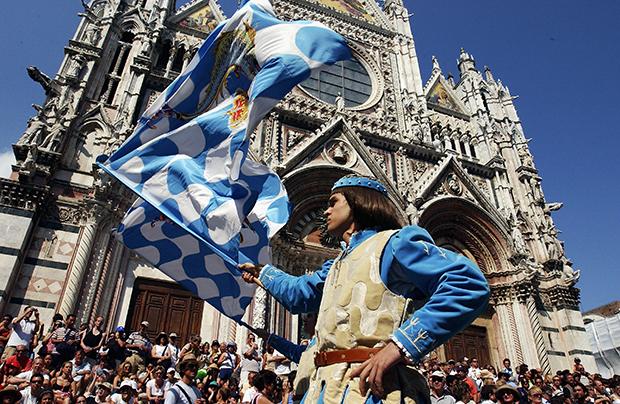 Кортео Сторико — праздничное шествие представителей всех контрад длится едва ли не половину дня. На фото знаменосцы контрады «Волны» (Onda) демонстрируют свое мастерство.