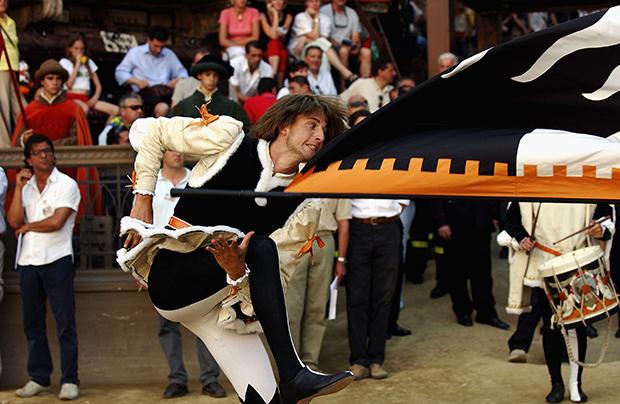 Знаменосцы жонглируют флагами, подбрасывают их вверх и выполняют акробатические номера. На фото представитель контрады «Волчицы» (Lupa).