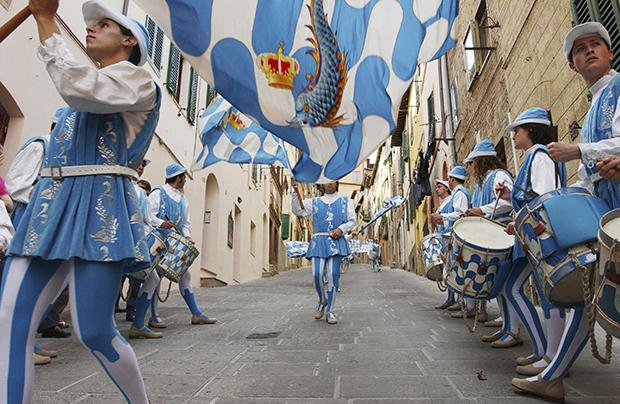 Праздничные шествия представителей отдельный контрад начинаются за несколько дней до самой гонки. На фото барабанщики и знаменосцы контрады «Волны» (Onda) маршируют по улицам города 28 июня 2004 года.