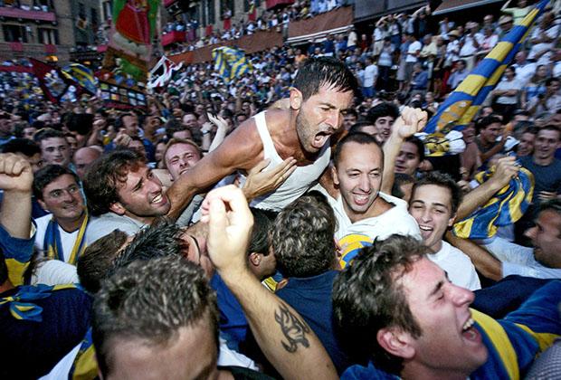 Победитель августовского Палио 2002 года Луиджи Брускелли в объятиях обезумевших от счастья представителей контрады «Черепаха» (Tartuca). Брускелли — один из самых успешных жокеев XXI века. Он выиграл 13 из 50 Палио, в которых участвовал.