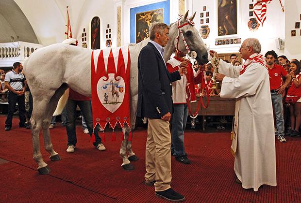Традиция благословлять лошадь и жокея утром перед гонкой прямо в главной церкви контрады соблюдается до сих пор, несмотря на возмущение верующих из других частей Италии. На фото церемония в контраде «Жирафа» (Giraffa) 16 августа 2011 года.