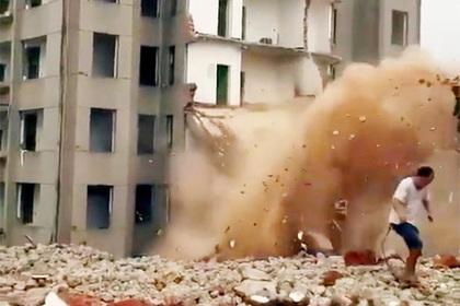 Китаец присел посмотреть на падающий дом и чуть не попал под него