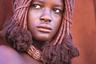 Представительница племени химба, проживающего в северной Намибии в области Кунене. Своей внешностью девушки химба подчеркивают значение крупного рогатого скота в жизни кочевого народа. Кожа на их теле и лицах выкрашена красной пастой, чтобы она мерцала как мех молодого теленка.  <br> <br> Наличие большого стада у представителя химба означает богатство и высокий социальный статус.
