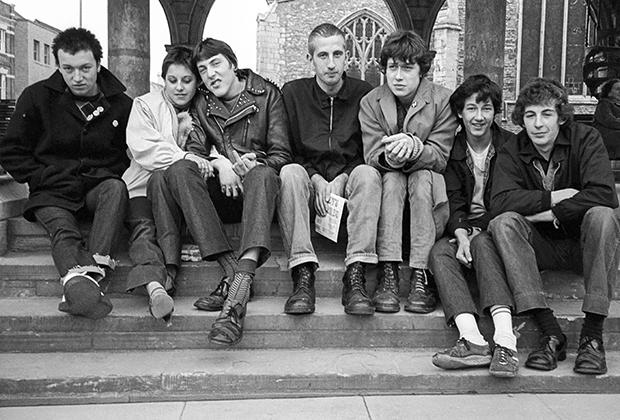 Панки на лестнице церкви в Англии. Из классических атрибутов панков начала 1980-х годов лишь ботинки, да кожаные куртки.
