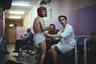 Санитар меняет подгузник пациенту психоневрологического интерната для престарелых и инвалидов № 3. Один из обитателей помогает ему.