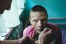 Санитар кормит пациента интерната в палате.