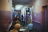 Интерьер психоневрологического интерната для престарелых и инвалидов № 3. Пациенты смотрят выпуск новостей в коридоре.