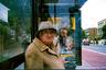 Портреты Лесли — не такие простые, как кажутся. Для понимания фотографии, нужно всмотреться в детали: здесь лицо старушки на остановке неожиданно контрастирует с лицами актеров на плакате, в то же время органично вписываясь в этот ряд.
