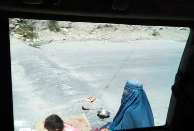 Посередине дороги на «лежачем полицейском», в трещине на асфальте сидела женщина с маленьким ребенком на коленях