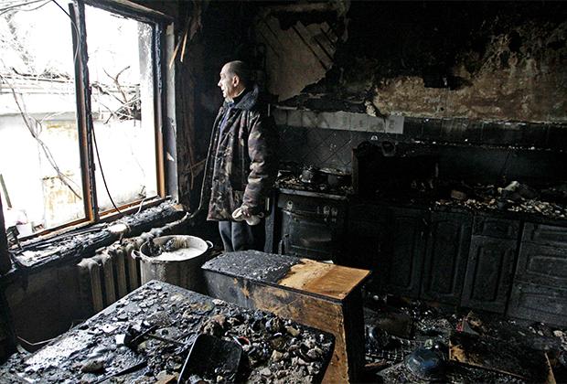 Житель Донецка осматривает свой дом, пострадавший в результате боевых действий