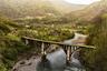 Мост над рекой Аалдзга, некогда соединявший город Ткуарчал и шахтерский поселок Акармара, давно утратил свое первоначальное назначение. Почти все здания Ткуарчала были разрушены войной, и сейчас он стал городом-призраком, больше похожим на декорации к фильму об апокалипсисе.