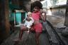 Девочка из фавелы Росинья в Рио-де-Жанейро.Трущобные кварталы находятся совсем рядом с фешенебельными районами, сюда довольно часто заходят туристы — любители острых ощущений. Иногда они их находят — фавела не полностью подконтрольна полиции. Официально население Росиньи перевалило за 70 тысяч человек, неофициально — называют разные цифры, вплоть до 200 тысяч.