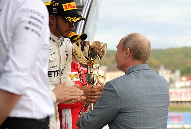 Президент России Владимир Путин вручает победный кубок Льюису Хэмильтону.