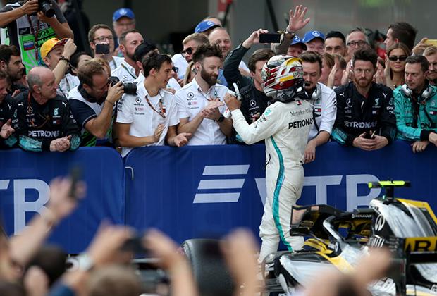 Победитель гонки Льюис Хэмильтон празднует успех вместе со своими механиками.